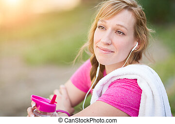 Young Fit Adult Woman Outdoors With Towel and Water Bottle in Workout Clothes Listening To Music with Earphones.