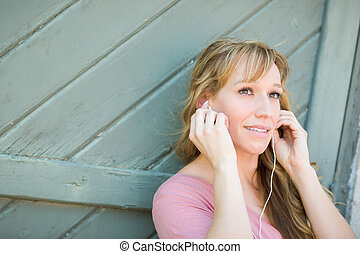 Outdoor Portrait of Young Adult Brown Eyed Woman Listening To Music with Earphones.