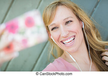 Young Adult Woman Wearing Earphones Taking a Selfie with Her Smart Phone.