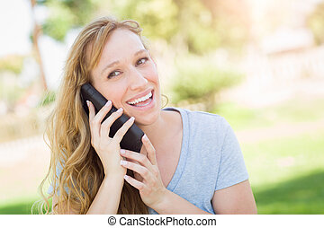 Young Adult Woman Outdoors Talking on Her Smart Phone.