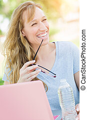 Young Adult Woman With Glasses Outdoors Using Her Laptop.