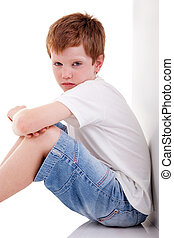 cute boy, sitting on the floor tired, isolated on white, studio shot