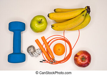 healthy eating concept. Dumbbell, rope, bananas, orange, measuring tape waist, oranges, red apple, green apple, on a white table. healthy lifestyle. sport. Fitness diet