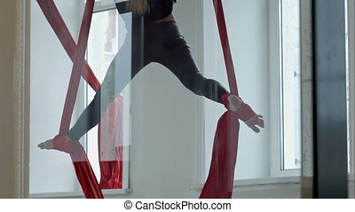Beautiful pole dancer doing twine in the air, using aerial...