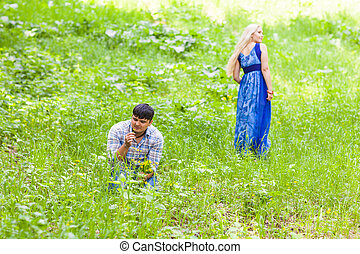 Young man picking up flowers for his woman.