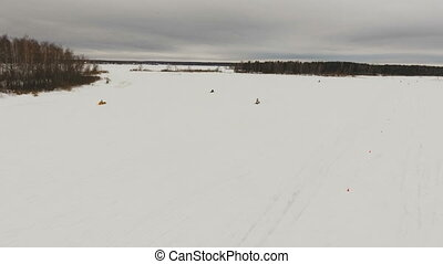 Racing on a snowmobile. - Group of people driving snowmobile...