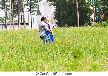 Happy young couple kissing in a summer park. Love concept. Vacation.