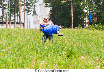 Young man carrying his girlfriend in his arms on grass field. Couple having fun in nature on a summer day.