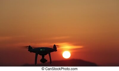 Remote controlled drone flying in air and sunset - Remote...
