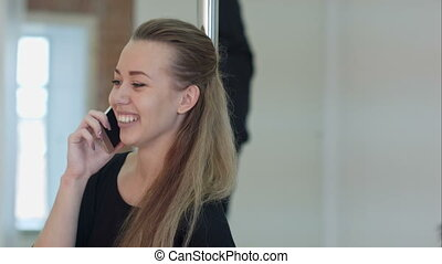 Happy pole dancer calling with a cell phone during a class