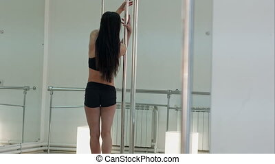 Young pole dance woman upside down in dance hall....