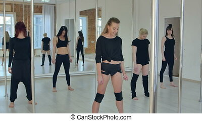 Attractive sport girls stretching before pole dance class in gym with windows