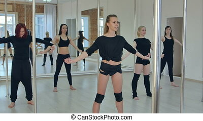 Group of sporty young women exercising at the studio, warming before pole dance class