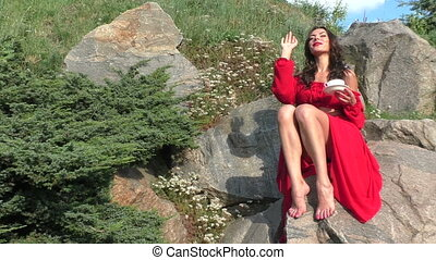 Woman in a red dress is sitting on a rock.