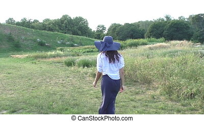Woman is walking in the field. - Woman in a big hat is...