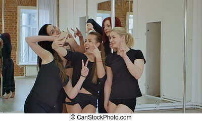 Group of young women taking a selfie during a pole dance class