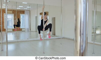 Flexible gymnast shows her twine on a pylon in a studio....