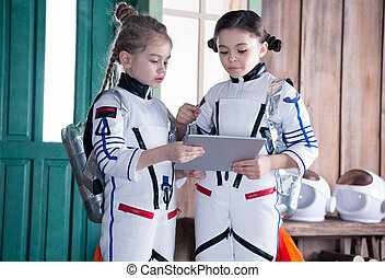 girls in astronaut costumes with jetpacks using digital...