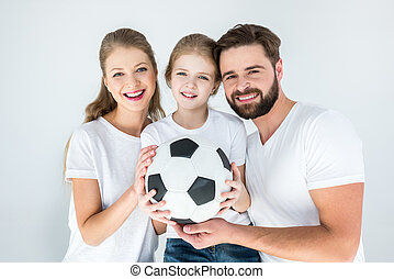 portrait of happy parents and daughter holding soccer ball...