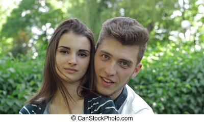 beautiful young couple in love looking and smiling on camera in the street