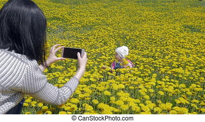 A young, attractive woman is taking pictures of a young child sitting on a field with dandelions on her phone. Mother and daughter. Slow motion