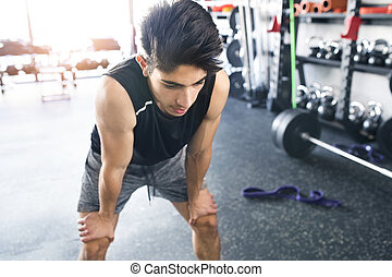 Young fit hispanic man in black sleeveless shirt in gym -...