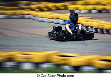 Shot is panned to emphasize speed. - Youth Go Kart Racer on...