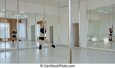 Sexy woman in a suit for the pole-dance gracefully with...
