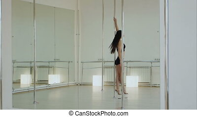 Beautiful woman performing pole dance in high heels shoes....
