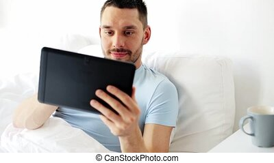 man with tablet pc drinking coffee in bed at home -...