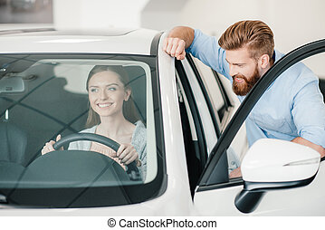 smiling young woman sitting in new car and man standing near
