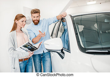 Happy couple holding catalog and choosing car in dealership salon