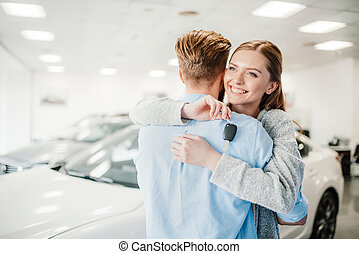 Happy couple holding car key and embracing in dealership salon