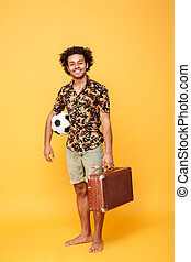 Smiling young african man holding suitcase and football -...