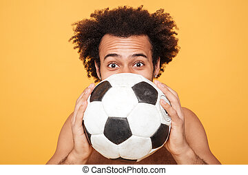 Young african man hiding face behind a foot ball - Close up...