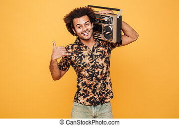 Man in summer clothes holding boombox on his shoulder -...