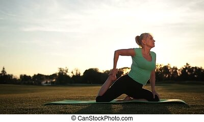 Fit woman training in yoga pigeon pose at sunset - Side view...