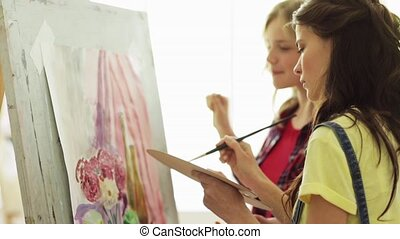 student girls with easel painting at art school