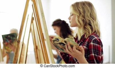 students with easels painting at art school