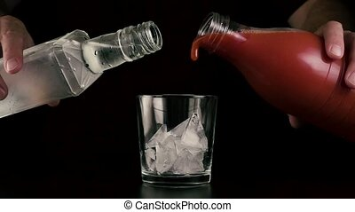Slow motion. Hands simultaneously pour juice and vodka -...