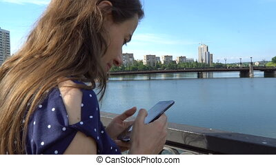 Beautiful woman with a smartphone near the river