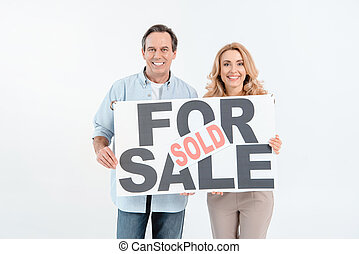 Happy mature couple holding signboard with lettering for sale and sold