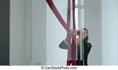 Beautiful pole dancer on red aerial fabric doing exercise