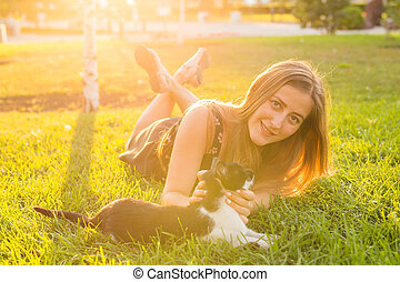 young woman with cat outdoors. young happy smiling woman...