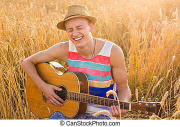 man outdoors playing acoustic guitar. A man is playing...