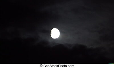 Full moon behind clouds at night.