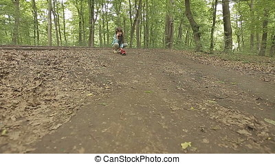 Little Girl Launching Fire Truck Car Toy on Hill in Forest -...