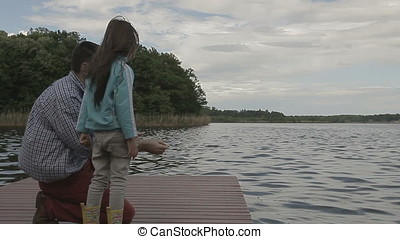 Father Teaching Daughter Throwing Stones in Water - Father...