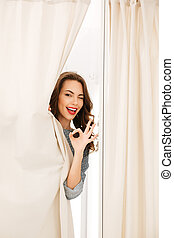 Happy young lady standing in fitting room - Picture of happy...