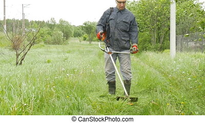 A man mows the grass near his country house. The camera...